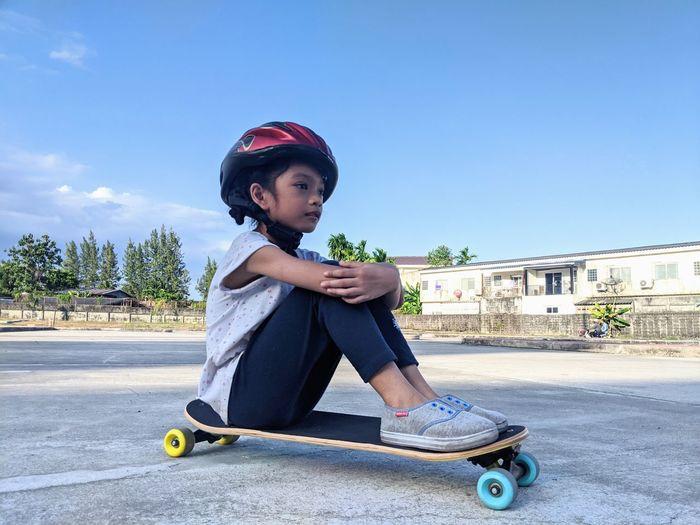 Portrait of boy sitting on skateboard