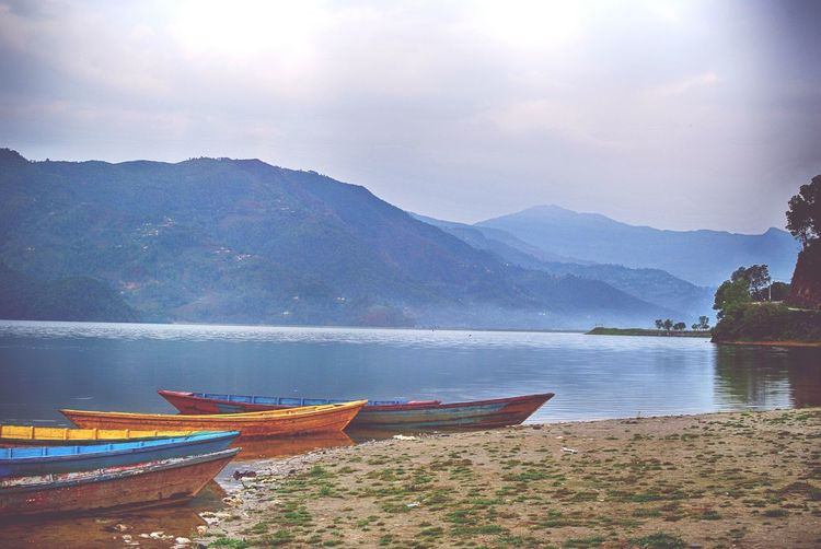 Moored boats in calm lake against mountain range