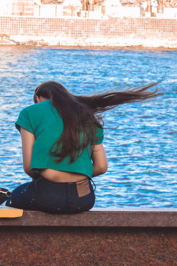 Rear View Of Woman Sitting On Ledge At Riverside
