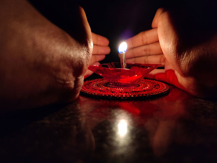 Close-up of hand holding lit candles