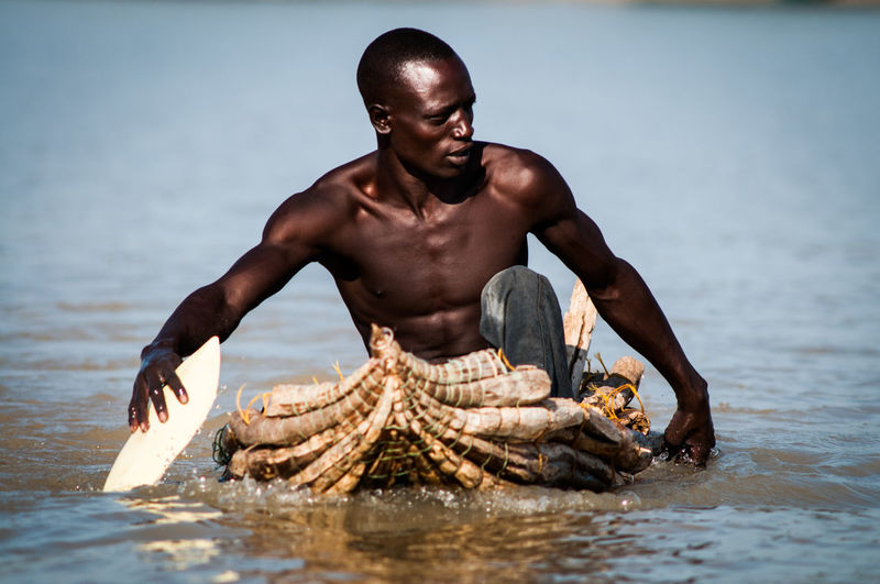 Kenya Beauty In Nature EyeEmNewHere Fisherman Fishing Boat Hardwork Into The Wild Lake Lake Baringo Muscles Nature Nature One Person Outdoors Paddeling Paddle Self Made Boat Shirtless The Great Outdoors - 2017 EyeEm Awards The Photojournalist - 2017 EyeEm Awards Water