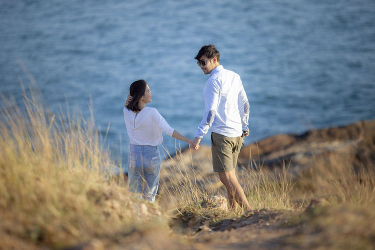 Rear view of couple holding hands standing against sea