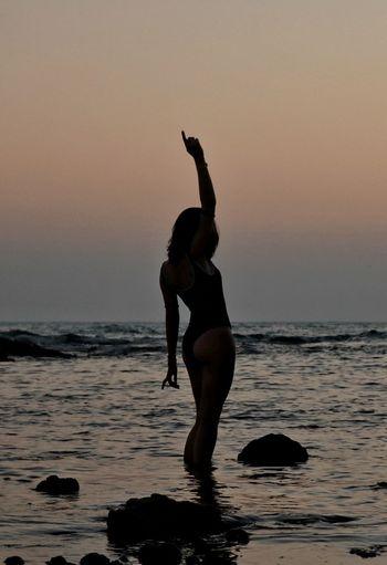 Full length of silhouette woman on beach against clear sky