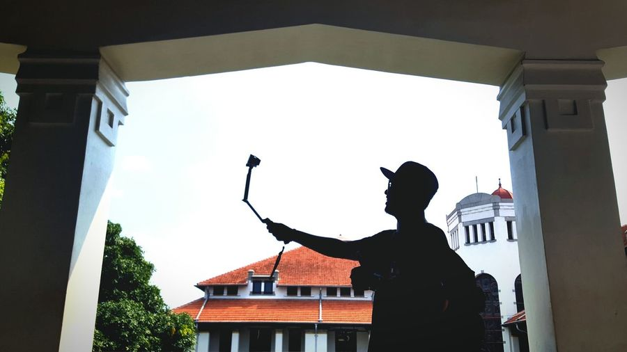 Low angle view of silhouette man taking selfie against buildings