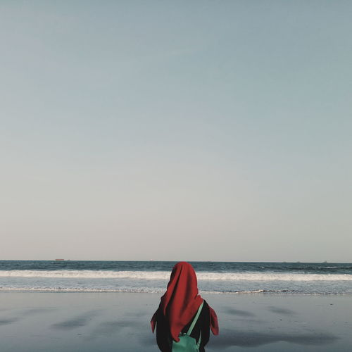 Rear view of woman in hijab standing at beach against clear sky