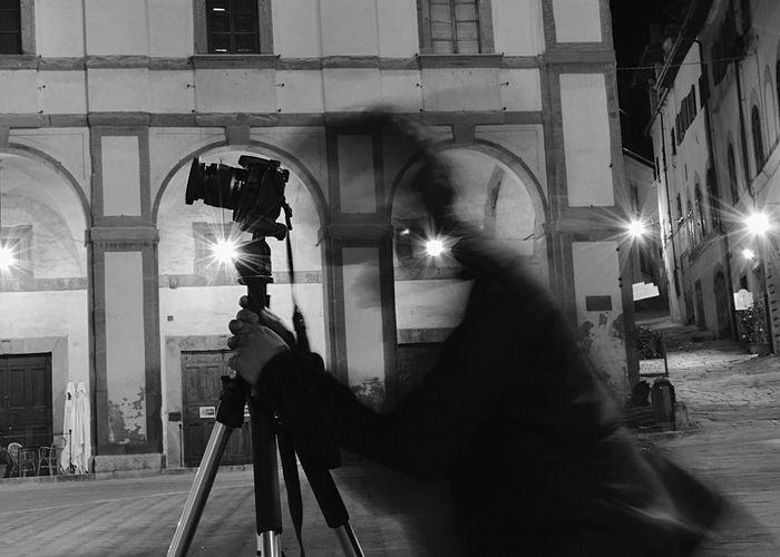 Man photographing woman in illuminated city at night