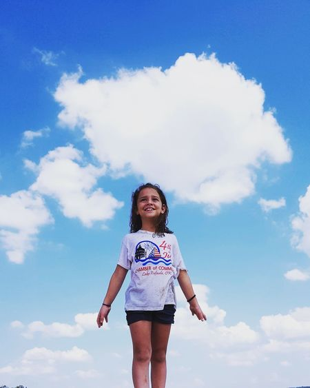 Low Angle View Of Girl Standing Against Blue Sky