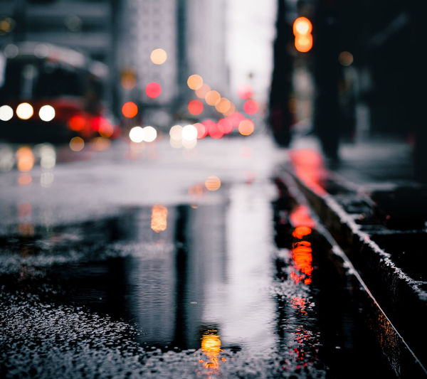 Reflection of illuminated city on wet road during rainy season