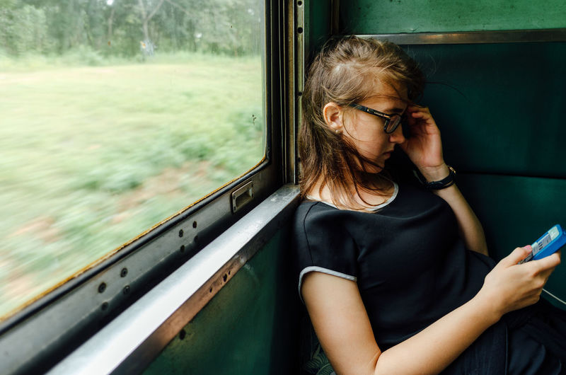 Midsection of woman looking through train window