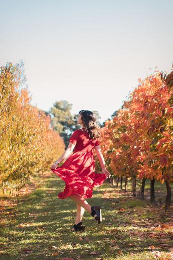 Full length of woman walking on autumn tree against sky