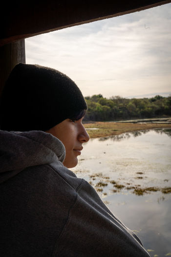 Side view of man looking at lake against sky