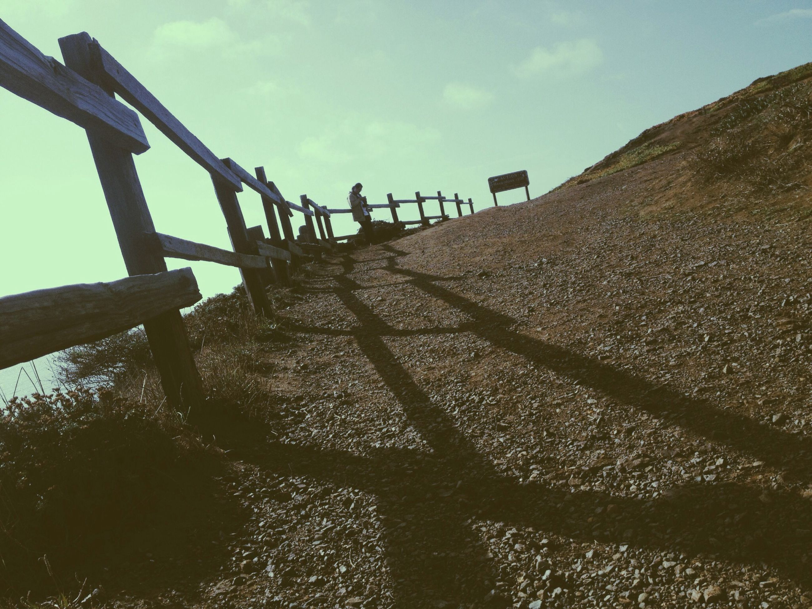 sky, water, railing, tranquility, low angle view, sunlight, sea, wood - material, metal, nature, protection, fence, safety, tranquil scene, outdoors, day, no people, security, shadow, pier