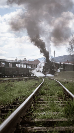 Railroad track by factory against sky