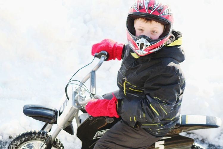 Portrait of boy riding motorcycle on snow