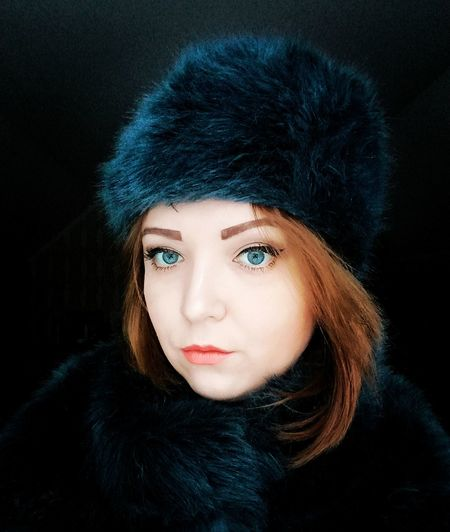 Close-Up Portrait Of Beautiful Woman Wearing Fur Hat Against Black Background