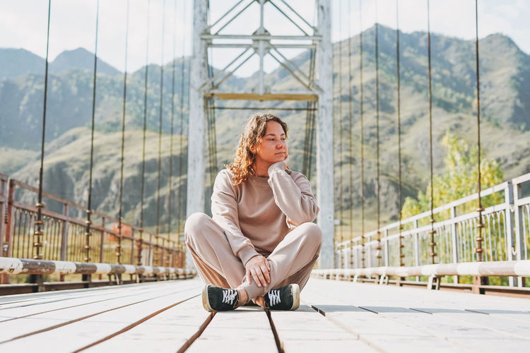 Young woman traveller in casual clothes sitting on horochowski bridge on katun river, altai