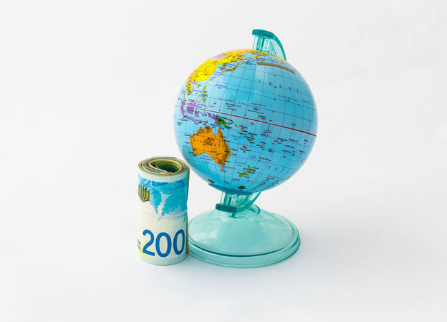A money box made in the form of a globe, the planet Earth with a money slot at the top stands near a rolled up and held together stack of Israeli banknotes of different value isolated on a white background. Business Currency Earning Earth Isolated Art Bank Banknote Buy Cash Coin Coins Design Exchange Finance Globe Israel Money Pay Planet Shekel Stock Studio Shot Wealth White Background