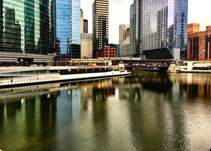 Chicago's colorful cityscape reflecting onto a nearly frozen river in winter. Waysofseeing Chicago Chicago River Chicago Loop Cityscape Downtown Chicago Reflection Rush Hour Skyscrapers Winter Architecture Building Exterior Building Exterior Architecture Built Structure City Cold Temperature Colorful Downtown District Modern Outdoors Pedestrian Riverwalk Sky Tower Travel Destinations Urban Skyline Mobility In Mega Cities