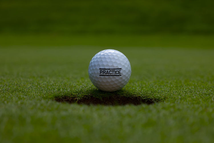 Golf Ball and Hole on Putting Green with Text Practice in Switzerland. Grass Sport Golf Ball Golf Ball Activity Green Color Selective Focus Leisure Activity Golf Course Green - Golf Course No People Close-up Day Still Life Outdoors Hole Golf Hole Low Angle View Pratice Text Putting Green Green Color Sunlight Simplicity