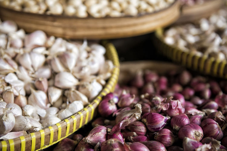 Close-Up Of Onions And Garlic For Sale At Market Stall