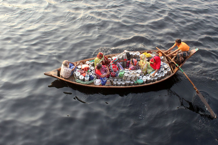 women are crossing river with a wooden boat to sale lunch box. Women Real People Rowboat Group Of People Lake Inflatable  Floating On Water Lifestyles Food And Drink People Men Sitting Outdoors Waterfront Nature High Angle View Mode Of Transportation Transportation Water Nautical Vessel International Women's Day 2019