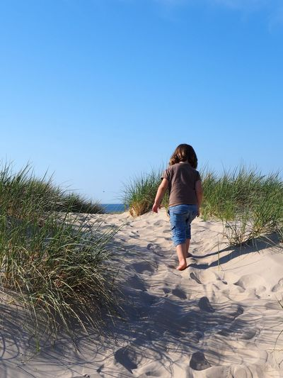 Taken in May 2018. Sky Sand Full Length One Person Rear View Clear Sky Land Nature Leisure Activity Real People Lifestyles Beach Plant Walking Day Sunlight Blue Casual Clothing Copy Space Outdoors Shorts Marram Grass Girl Boy Child Childhood Dune Dunes Northsea North Sea Up Seaview Blue Sky