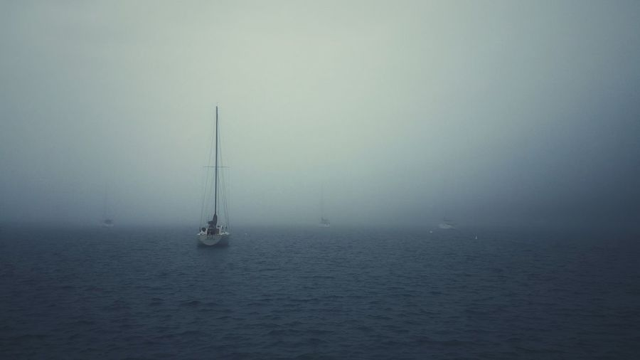 Boats Moving On Lake During Foggy Weather