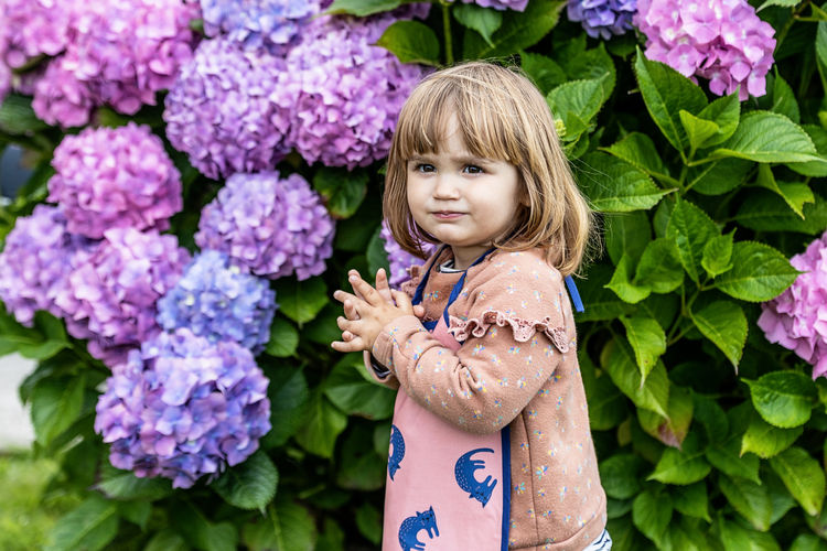 Portrait of girl standing on purple flowering plants