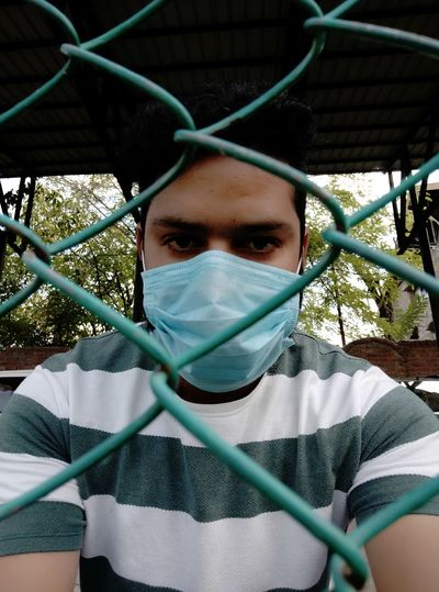 Portrait of man wearing mask  standing by fence