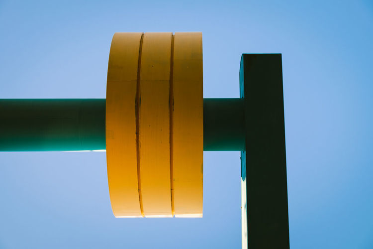 Low angle view of yellow metal against clear blue sky