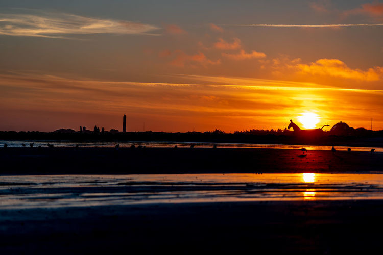 """Sunset on Blåvand beach with the bunker """"Horses"""" as can also see the lighthouse on the left. Beauty In Nature Cloud - Sky Idyllic Non-urban Scene Orange Color Outdoors Reflection Romantic Sky Silhouette Sky Sunset Water"""