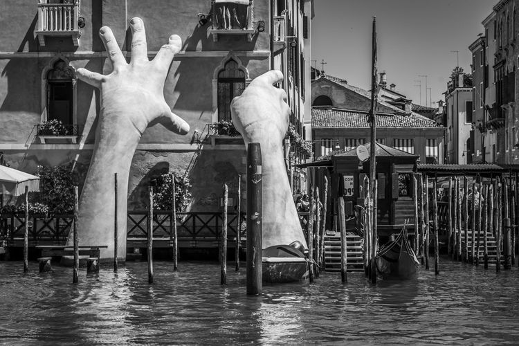 """Artwork titled """"Support"""" emerges from Grand Canal, by Lorenzo Quinn, black and white. The contemporary sculpture of giant hands was unveiled during the opening of the 2017 Venice Biennale. 2017 BIG Be. Ready. Famous Giant Gondolas Grand Canal Hands Quinn Reflection SUPPORT Venice, Italy Architecture Art Biennale Black And White Change City Day Lorenzo Monumental  Outdoors Rise Speedboat Water"""