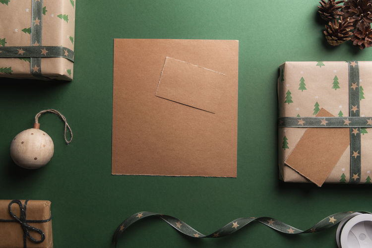 Unwritten vintage brown paper on a green background, surrounded by Christmas presents and decorations. Table Green Color Paper Directly Above Brown Cardboard Christmas Gift Xmas Gift Box Copy Space Christmassy Holidays Gifting Winter Holidays Wrapped Gift Family Time Blank Paper Note