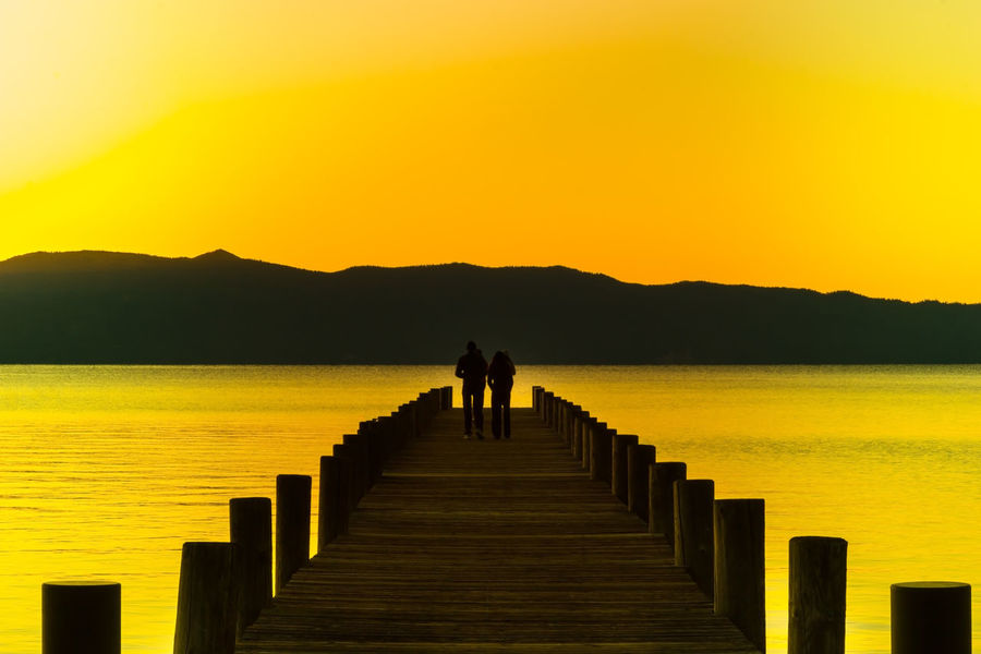 Lake Tahoe, Ca Beauty In Nature Centered Centered Perspective Day Full Length Jetty Lake Tahoe Men Mountain Nature Outdoors People Pier Real People Scenics Sea Silhouette Sky Sunset Tranquil Scene Tranquility Two People Water