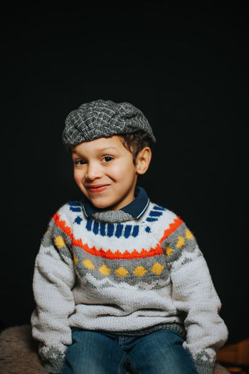 Portrait of smiling boy against black background