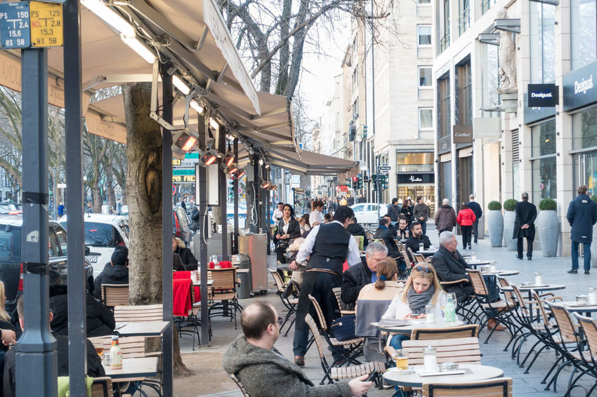 DUESSELDORF, GERMANY - MARCH 12, 2017: Unidentified shoppers stroll along the Königsallee and pass a scenic cafe with unidentified individuals Adult Architecture Building Exterior Built Structure City Citylife Day Düsseldorf Königsallee Large Group Of People Life Style Luxury Men Outdoors P People Real People Rhein Shopping Sitting Table Visitors Women