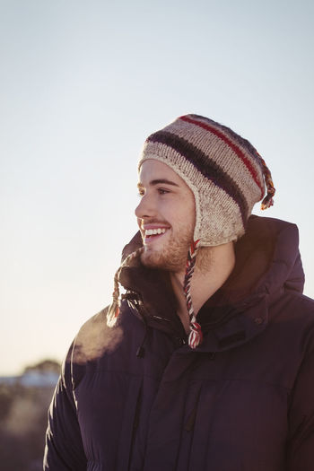 Portrait of young man wearing hat against sky during winter