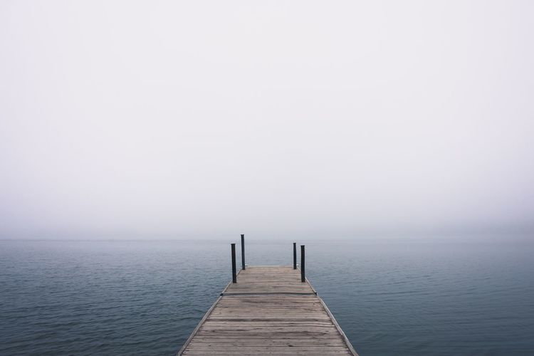Dock on the water in the fog MidWest Rural Country Seeing Silence Ways Of Seeing Minnesota Lake Haze Fog Water Pier Beauty In Nature Copy Space The Way Forward Sky Tranquil Scene Scenics - Nature Wood - Material No People Clear Sky Jetty Nature Horizon Idyllic Horizon Over Water Tranquility Direction Sea
