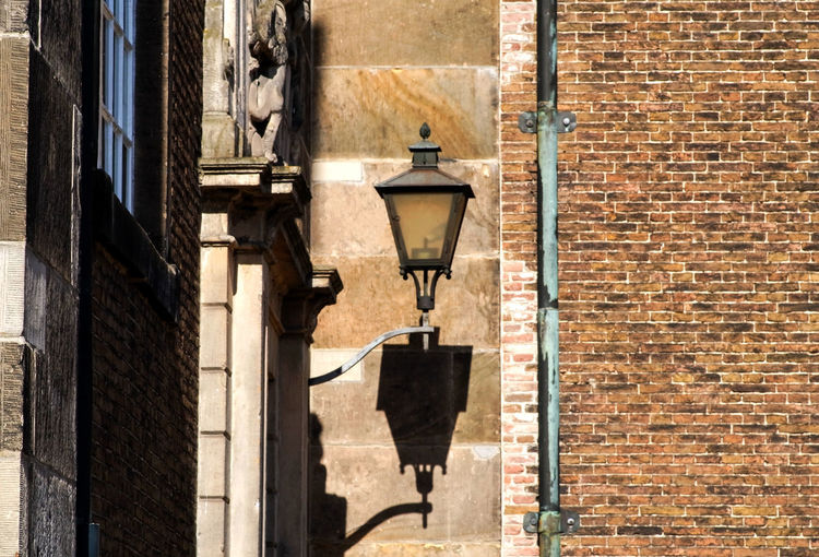 Street light against building wall