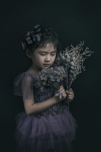 Girl With Plants Against Black Background