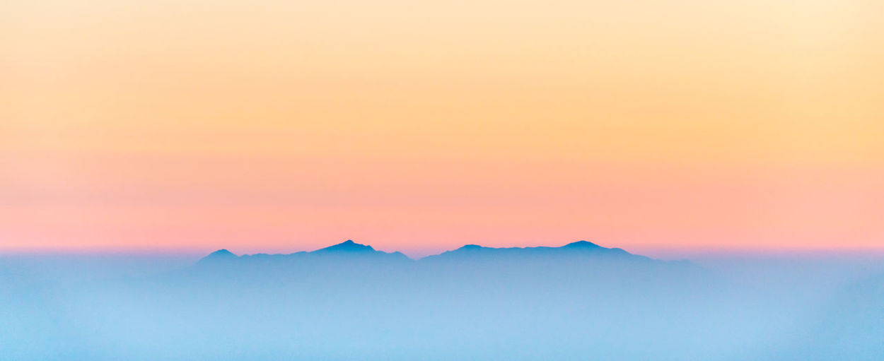Scenic view of mountains against romantic sky at sunset