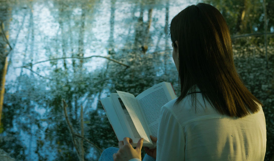 #Lake #book #coffestoryy #coffee #portrait #publicidad #woman # Activity Adult Black Hair Book Focus On Foreground Hair Hairstyle Holding Human Hair Leisure Activity Lifestyles Long Hair One Person Outdoors Plant Publication Reading Real People Rear View Tree Women