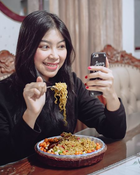 Portrait of smiling young woman using mobile phone while sitting on table