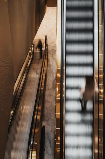 High Angle View Of Man Walking On Escalator