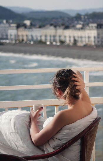 Woman having coffee while sitting against sea in city