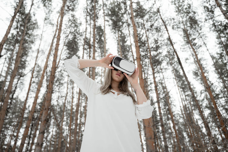 Low angel view of woman using vr against trees