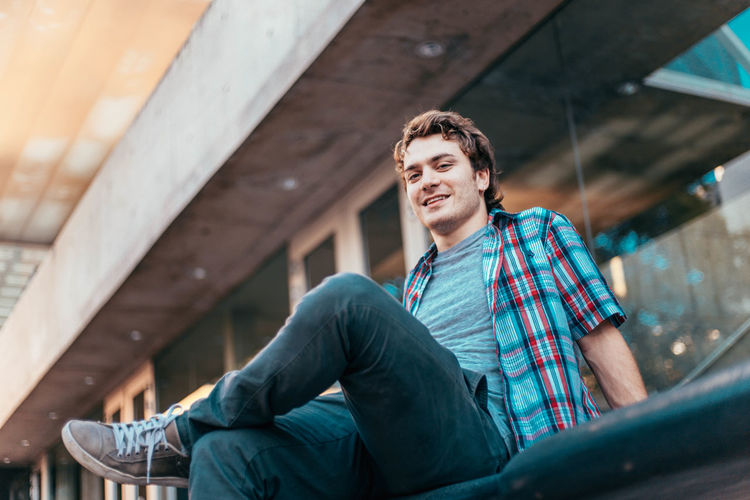Low angle portrait of man smiling while sitting on seat against building
