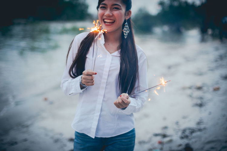 Adult Burning Casual Clothing Emotion Fire Fire - Natural Phenomenon Focus On Foreground Front View Hairstyle Happiness Holding Leisure Activity Lifestyles Nature One Person Outdoors Smiling Sparkler Standing Three Quarter Length Waist Up Warm Clothing Young Adult Young Women