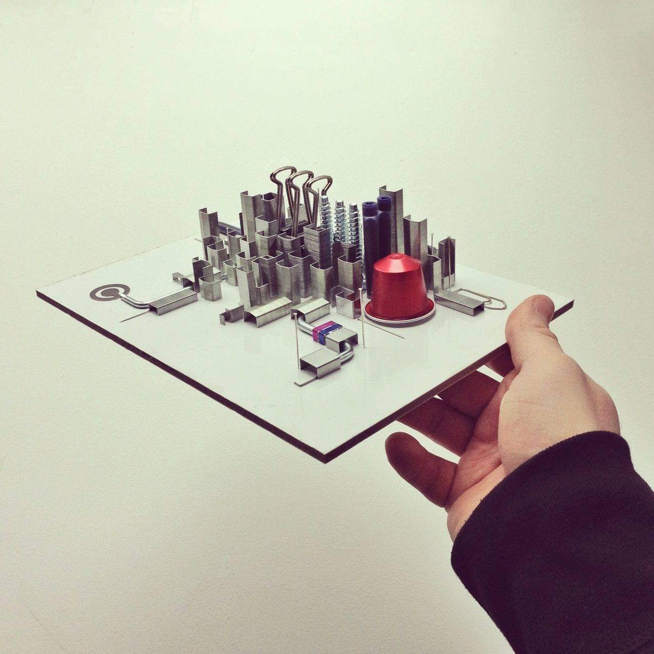 Hand holding metallic objects representing urban cityscape