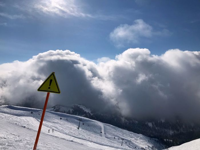 Road sign against snowcapped mountains during winter